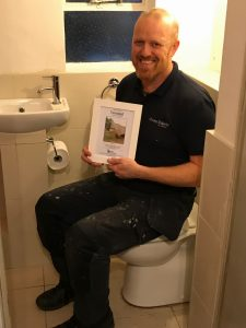 Eden Warren, Operations Director in Threesixty's showroom loo with Threesixty's Toilet Twinning certificate